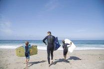 Vue arrière de l'homme et de deux fils descendant la plage et portant des bodyboards, Laguna Beach, Californie, États-Unis — Photo de stock