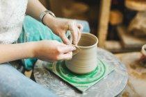 Female hands pottering pot — Stock Photo