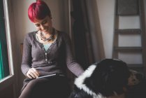 Young woman at home using digital tablet, stroking dog — Stock Photo