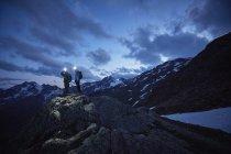 Senderismo joven pareja mirando escarpadas montañas por la noche, Val Senales Glacier, Val Senales, Tirol del sur, Italia - foto de stock