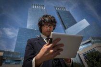 Молодой бизнесмен за столом возле офисных зданий — стоковое фото