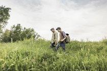 Vista lateral del hombre y el niño con gorras planas caminando en hierba alta llevando caña de pescar - foto de stock