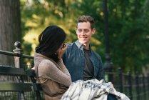 Metà donna adulta seduta sulla panchina del parco fotografare fidanzato sulla fotocamera reflex — Foto stock