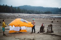 Two young men setting up tent on beach, Huntington Lake, California, USA — Stock Photo
