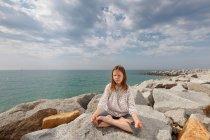 Девушка медитирует на скалах на пляже — стоковое фото