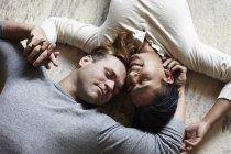 Вид сверху на гей-пару, лежащую на полу в противоположных направлениях — стоковое фото