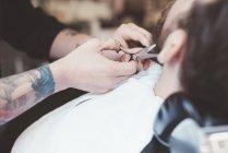 Primo piano del barbiere taglio barba cliente nel negozio di barbiere — Foto stock