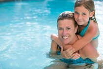 Portrait of girl and mother in outdoor swimming pool — Stock Photo