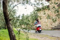 Rear view of young couple riding moped in village, Florence, Italy — Stock Photo