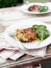 Plate of fried vegetable cake with basil leaves and fork — Stock Photo
