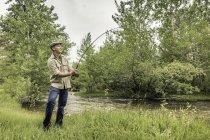 Young man wearing flat cap on river bank fishing — Stock Photo