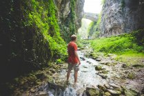 Man standing in stream, rock hills and stone bridge in background, Garda, Italy — Stock Photo