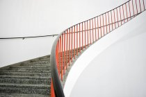 Interior view of Curved stairs with red banister — Stock Photo