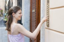 Mid adult woman pressing holiday apartment doorbell, Sardinia, Italy — Stock Photo