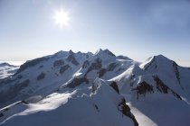 Aux sommets enneigés des montagnes Rocheuses avec brillant soleil — Photo de stock