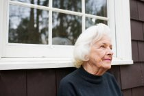 Portrait of senior woman outside house looking away — Stock Photo