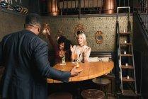 Multiethnic Friends meeting in pub — Stock Photo
