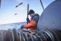 Fisherman preparing net on trawler — Stock Photo