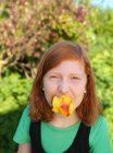 Jeune fille tenant pêche dans la bouche, portrait — Photo de stock
