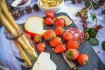 Morangos maduros e o queijo na mesa de piquenique — Fotografia de Stock