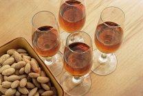 Vasos de jerez y almendras en plato sobre mesa - foto de stock