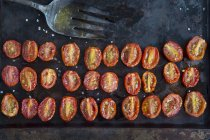 Vista superior de las filas de tomates asados a la mitad en estaño para hornear - foto de stock