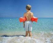 Vista posteriore di boy paddling con bracciali — Foto stock