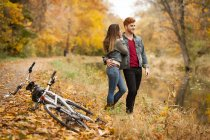 Romantic young couple on riverside in autumn — Stock Photo