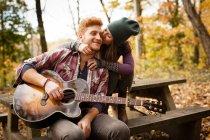 Romantische junges paar Gitarre spielen auf picknickbank im herbstlichen Wald — Stockfoto