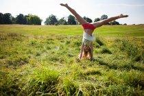 Jovem fazendo um suporte de mão em um campo — Fotografia de Stock