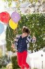 Menina de dez anos pulando excitadamente com um monte de balões — Fotografia de Stock