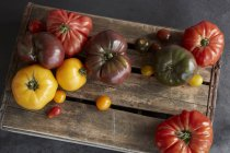 Selection of heirloom tomatoes on wooden board — Stock Photo