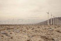 Fileiras de turbinas eólicas em paisagem seca sob céu nublado — Fotografia de Stock