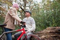 Пара в парке с велосипедом — стоковое фото