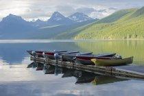 Molo con barche ormeggiate e paesaggio montano — Foto stock