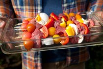 Man holding Tray of raw kebabs for grill — Stock Photo