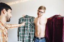 Чоловічий пара, середині дорослий чоловік, просять допомоги вибираючи сорочка — стокове фото