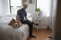 Cute corgi dog lying on bed watched by young man — Stock Photo