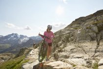 Young couple with  mountain bikes on path at Val Senales Glacier, Val Senales, South Tyrol, Italy — Stock Photo