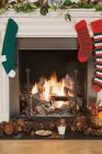 Christmas stockings hanging on decorated fireplace — Stock Photo