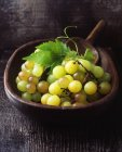 Bunch of green grapes in vintage wooden bowl — Stock Photo