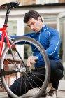 Mid adult man adjusting bicycle wheel — Stock Photo