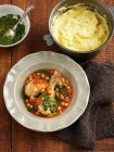Bowl of chicken and chickpeas wit mashed potatoes on table — Stock Photo