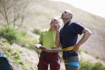 Rock climbers wearing safety harness looking up — Stock Photo