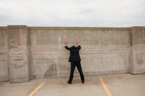 Businessman standing with hands against wall — Stock Photo