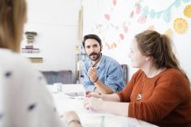 Female and male designer having brainstorm meeting in printing press studio — Stock Photo