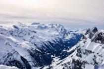 Cobertas de neve de montanhas sob céu nublado — Fotografia de Stock