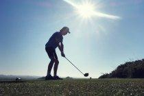 Niño jugando al golf durante el día - foto de stock