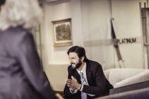 Businessman sitting in armchair talking to businesswoman — Stock Photo