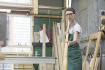 Woman in workshop checking alphorn tube — Stock Photo